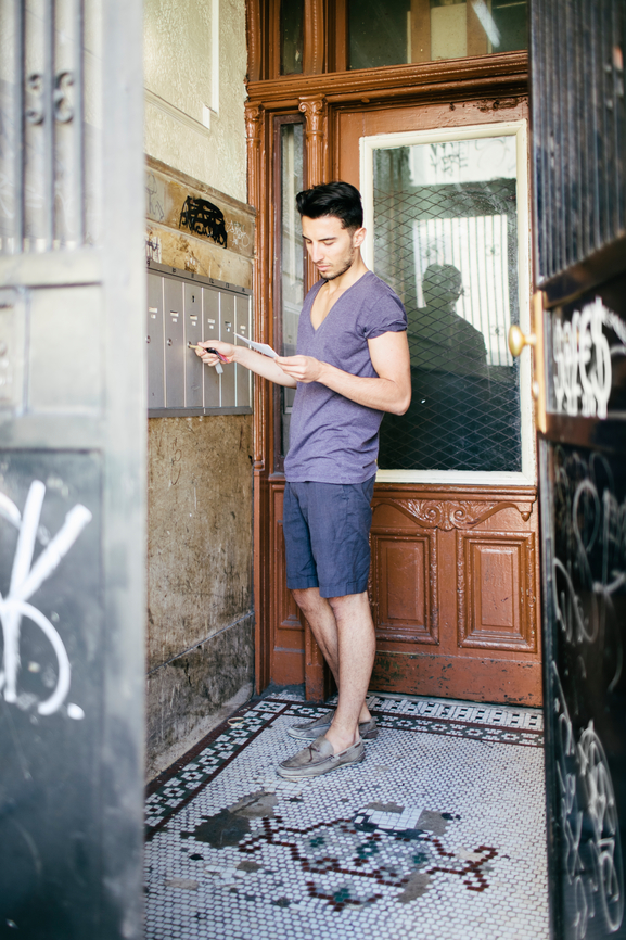 Young Man Collecting Mail in Old Apartment Building in New York