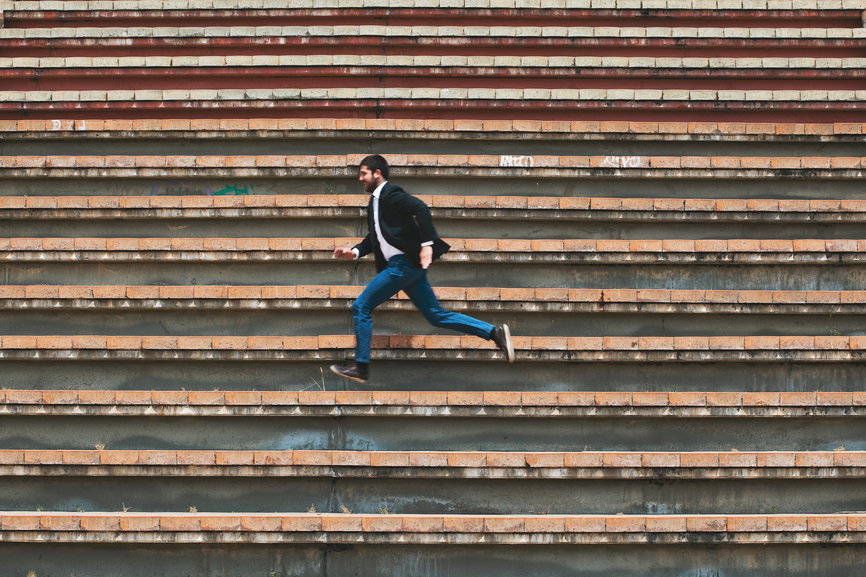 Young businessman running on stairs