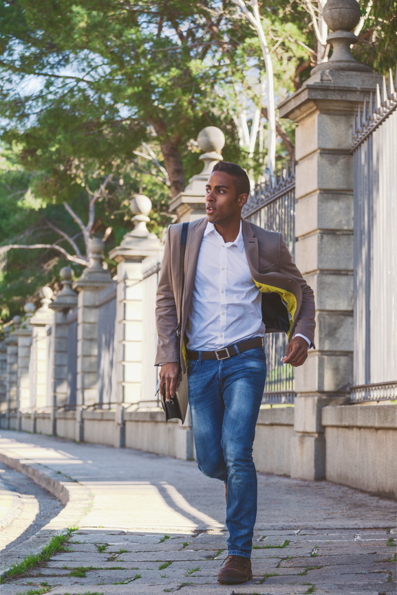 Black businessman running in front big gate in the park.