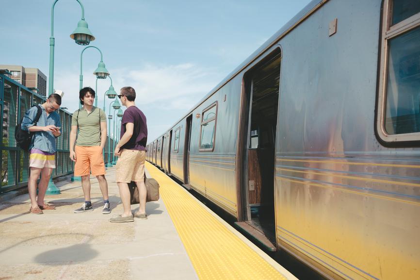 Group of Young Men Friends in Rockaway Beach Subway Train Statio