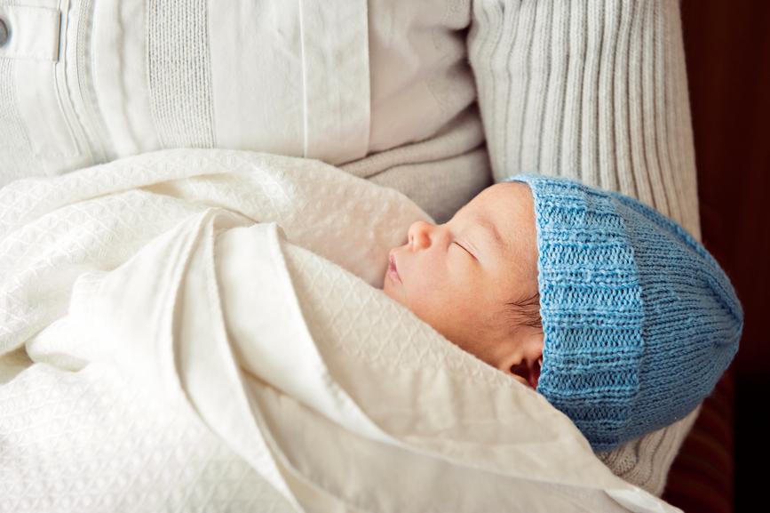 sleeping newborn held in dad's arms