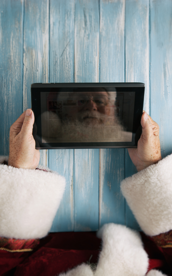 Santa Using Digital Tablet At Christmas