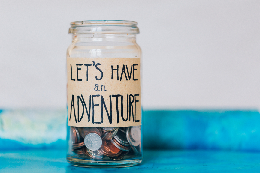 "Money jar with coins on atlas labelled ""Let's Have An Adventure"""