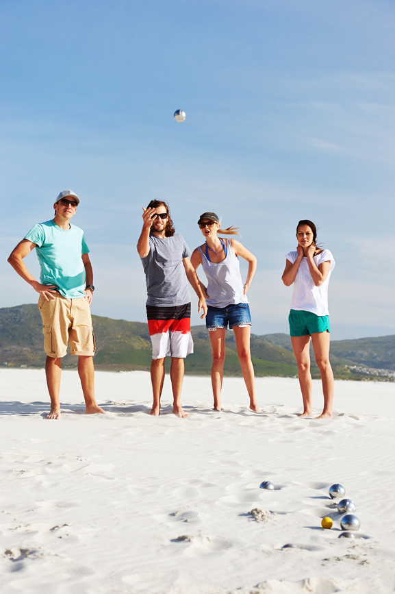 group of friends play boules at the beach having fun laughing and enjoying the game