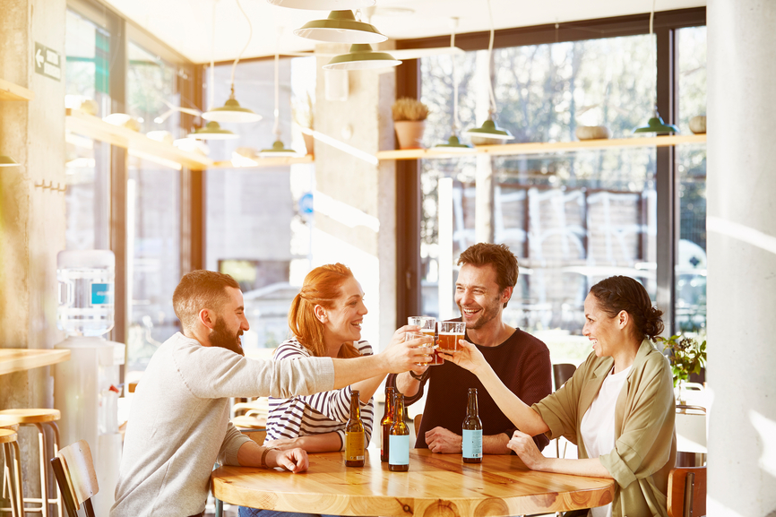 Happy business friends toasting beer glasses in restaurant