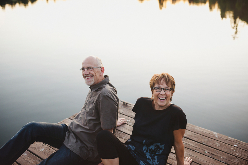 Content middle aged, retired couple sitting together laughing ou