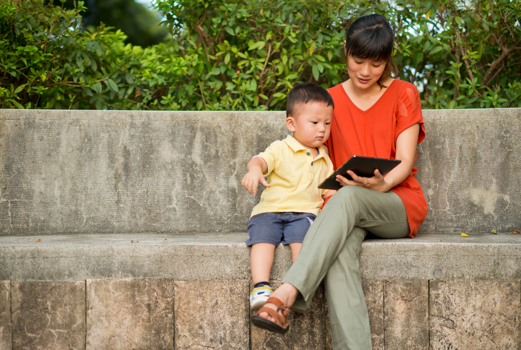 Mother and boy look at tablet in the park