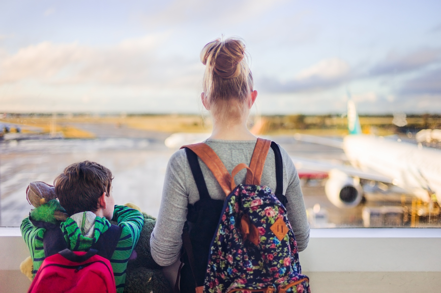 Two children look out an airport window at the plane they are waiting to board