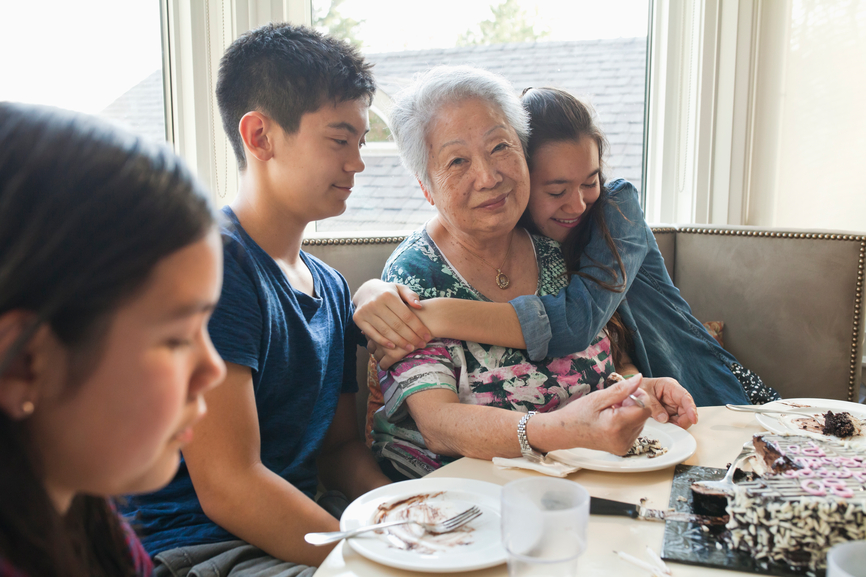 Grandmother eating cake on her 80th birthday with grand children.