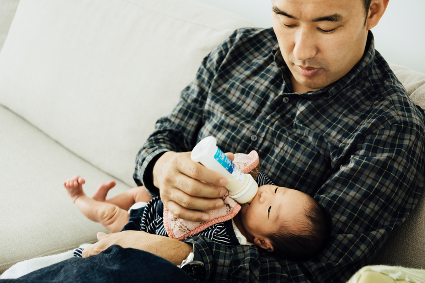 Asian father, feeding milk to a 10-day-old newborn baby girl