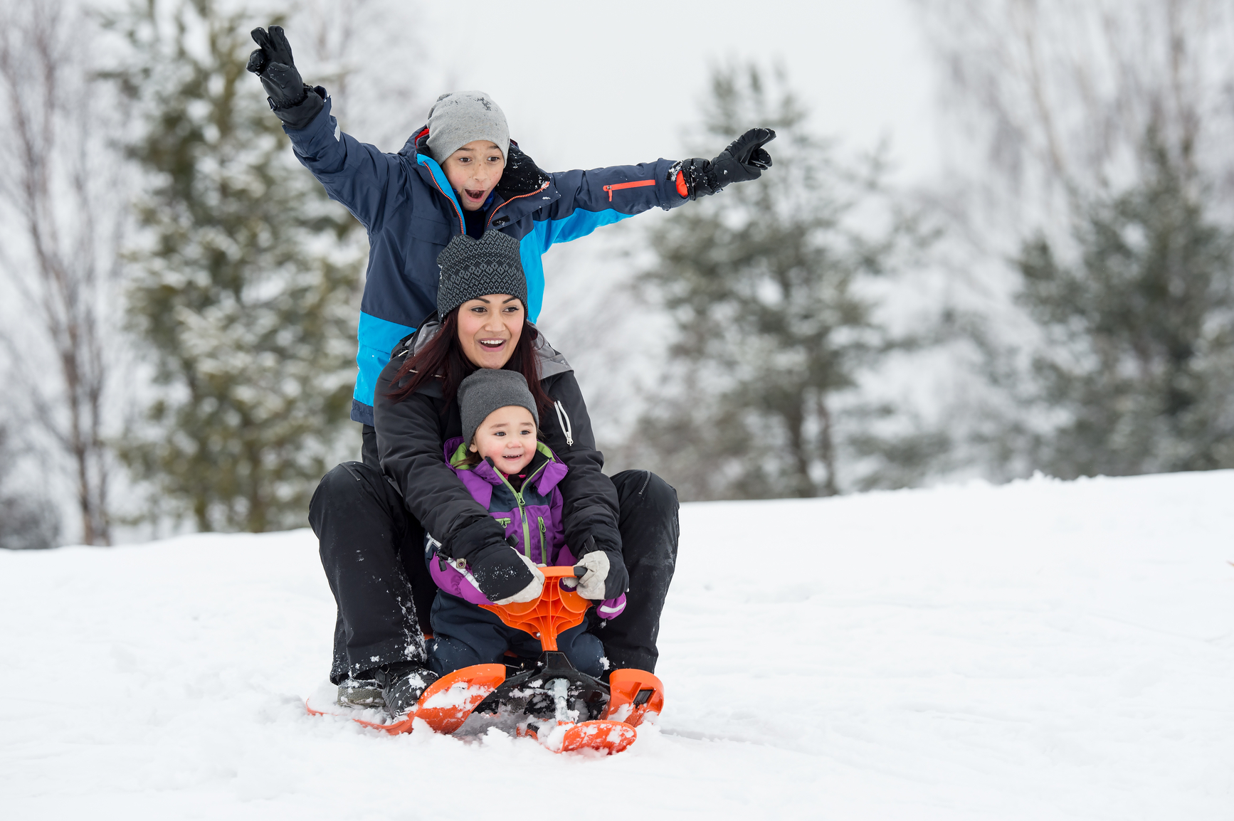 a mother having fun wiht her children in the winter