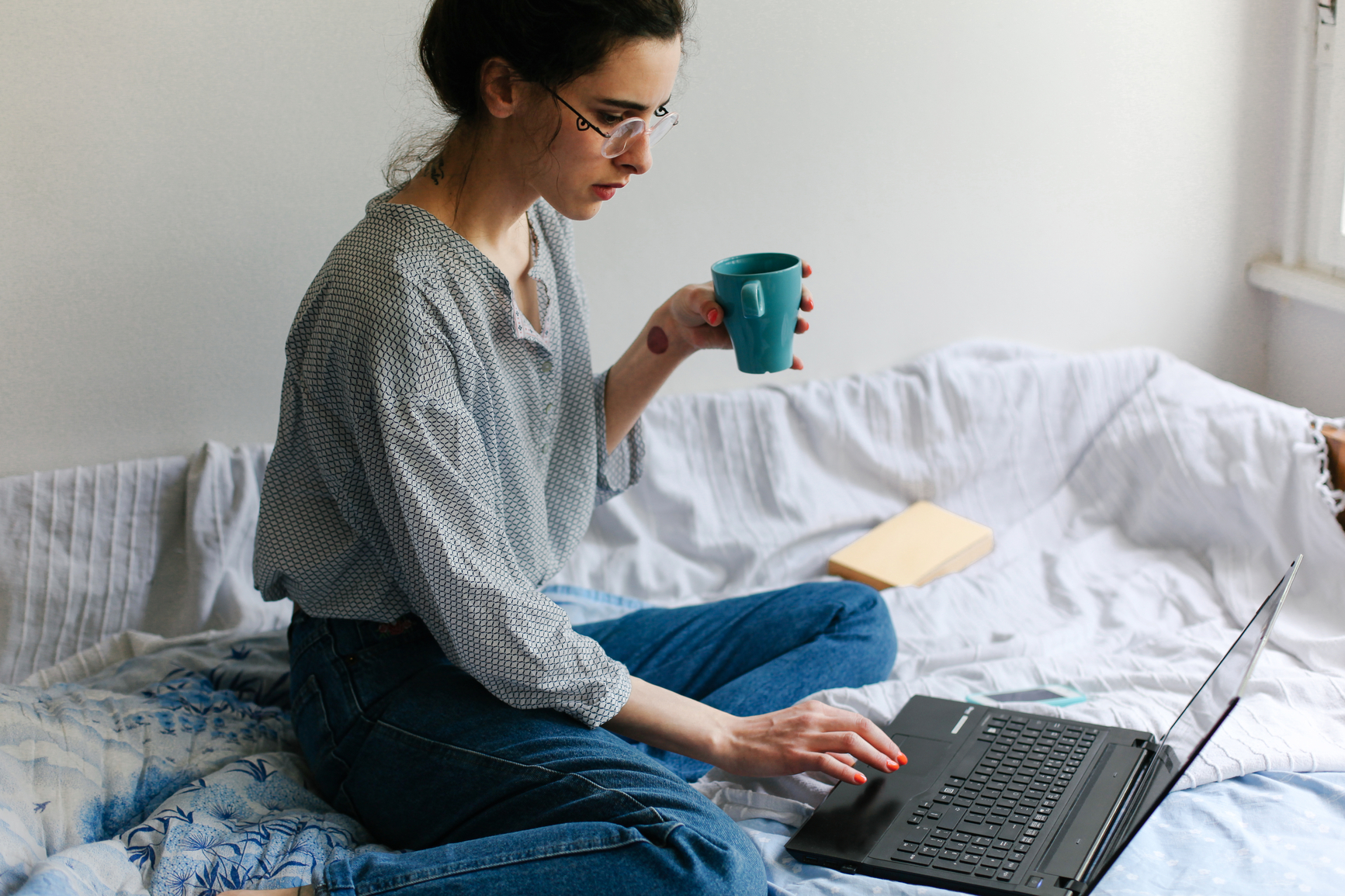 Woman drinking coffee on the bed, using her laptop