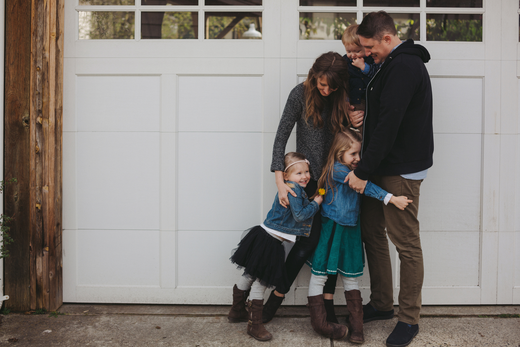 Young family of five enjoying time -hugging together outside nea