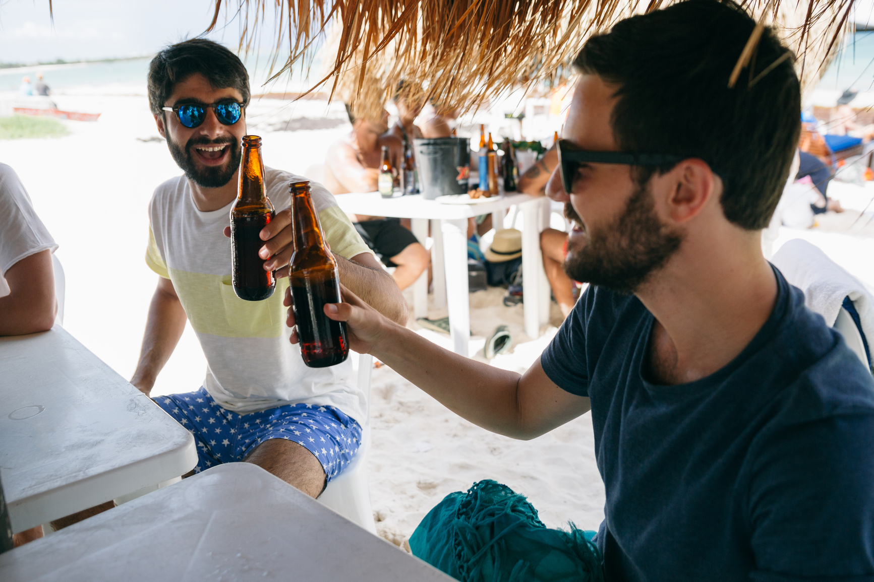 Two friends toasting their bottle of beers on a beach bar
