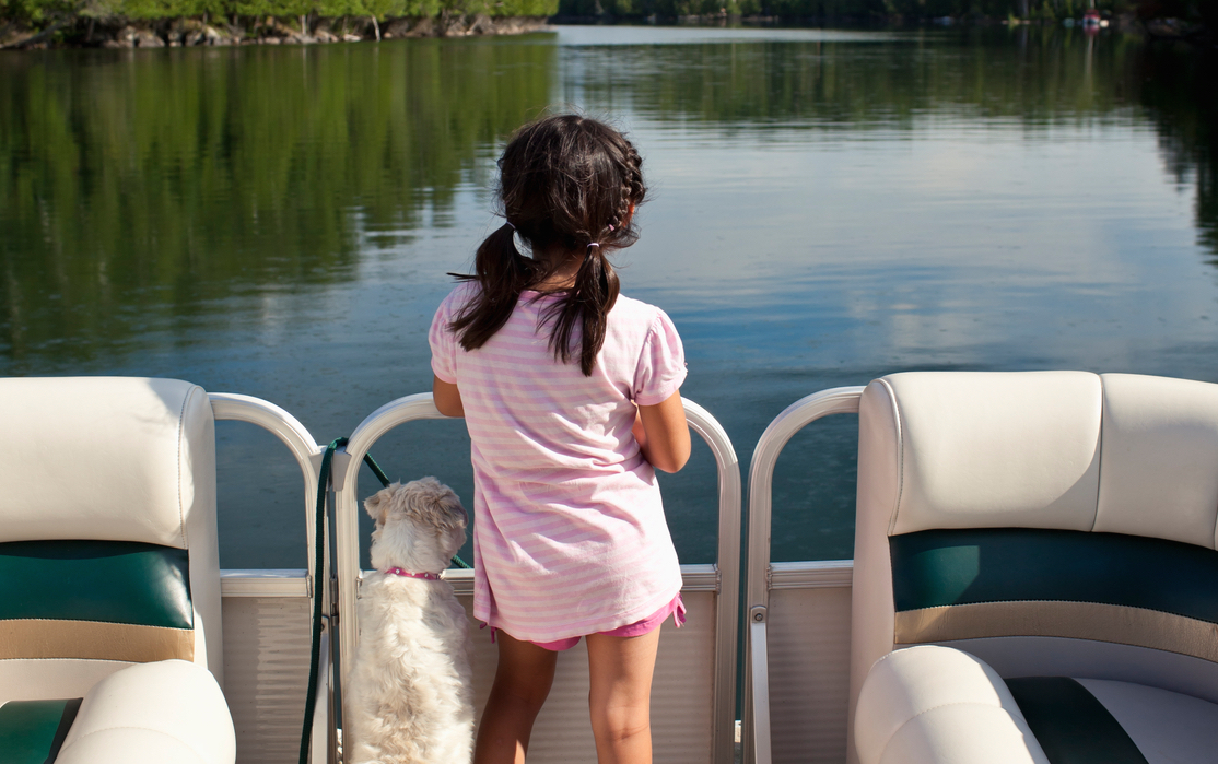 Girl and her dog enjoy a pontoon boat ride, taking in the scenery.