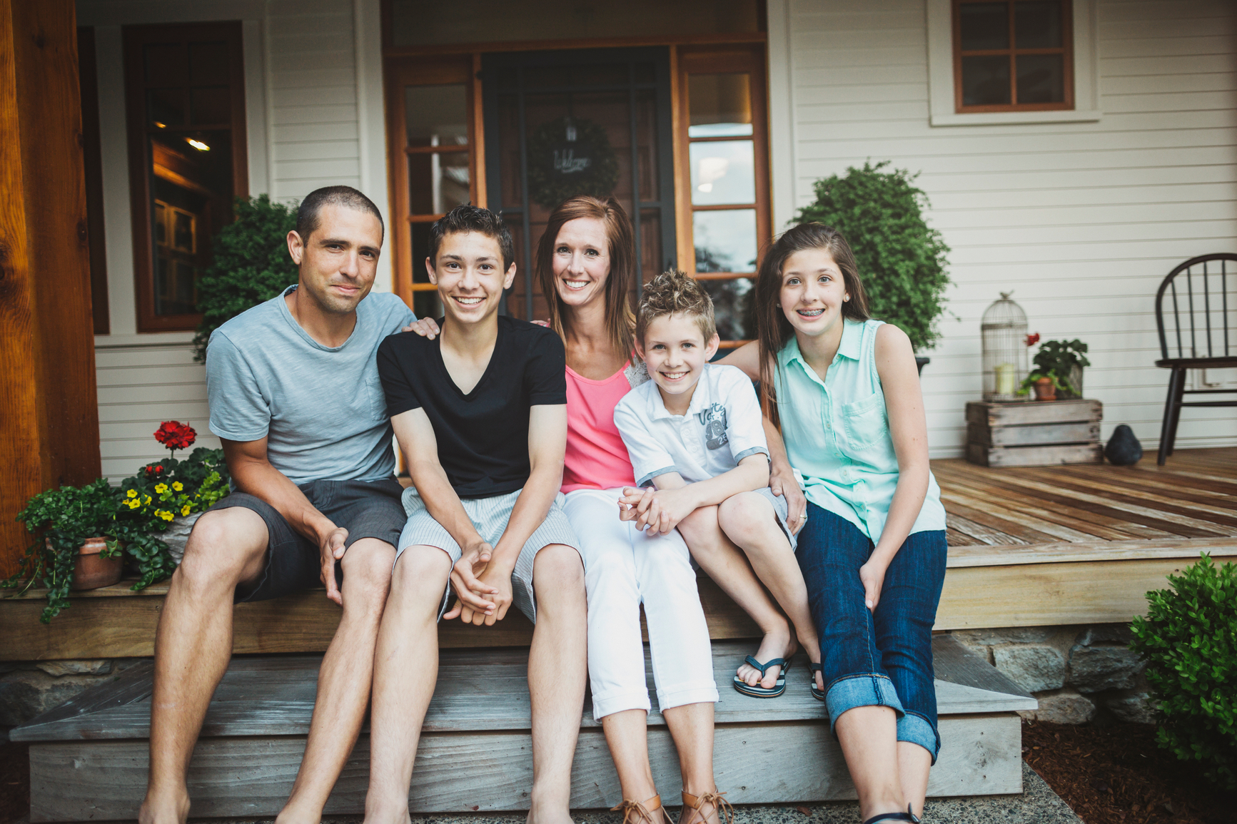 Portrait of happy, loving family with teenagers at home on front