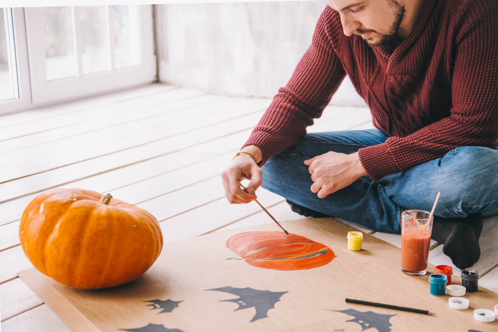 Man painting pumpkin with gouache