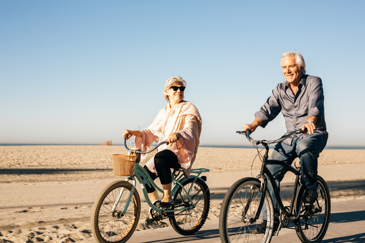 Seniors biking on the beach