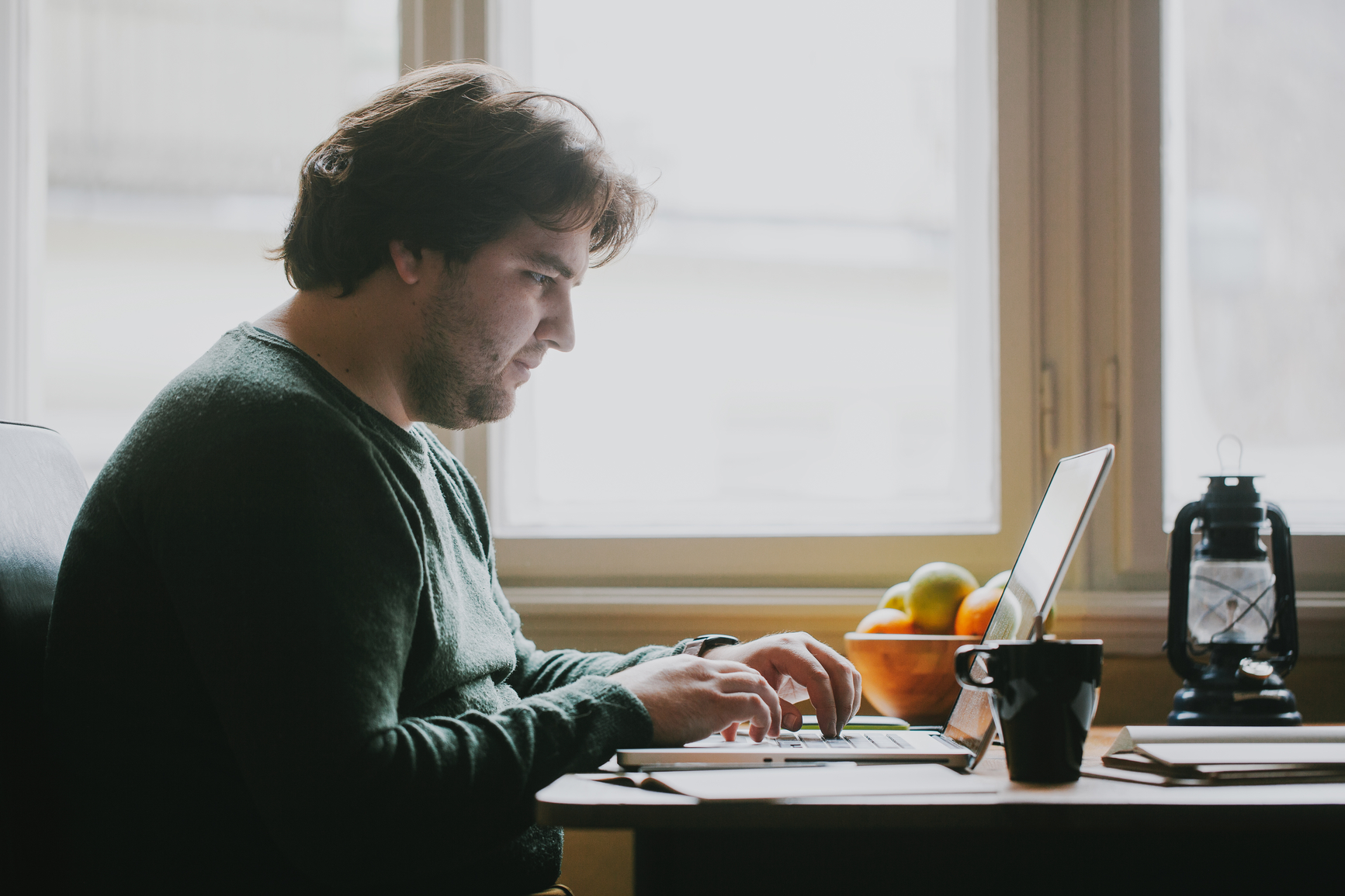 Caucasian man working on his laptop at home.