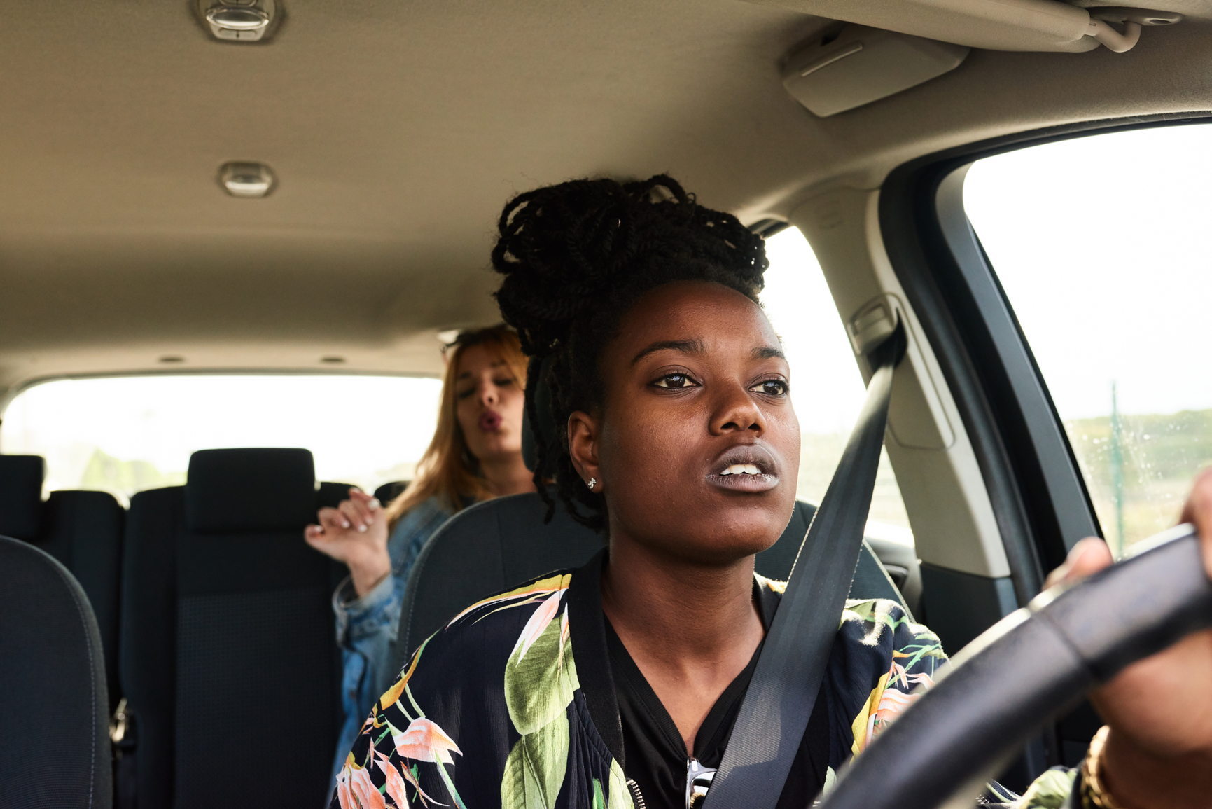 Portrait of concentrated girl driving car while her friend singing and having fun on backseat.