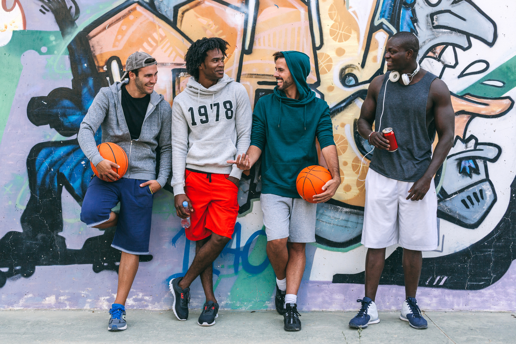Friends Rests Over a Graffiti Painted Wall After a Street Basketball Game