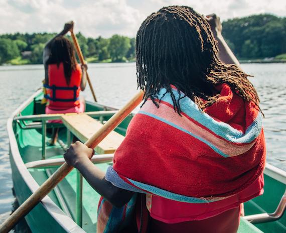 Two black girls paddling in a canoe